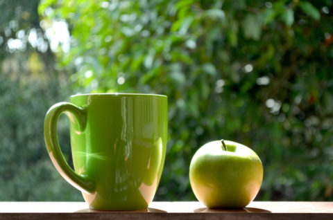 A green mug and a green apple.
