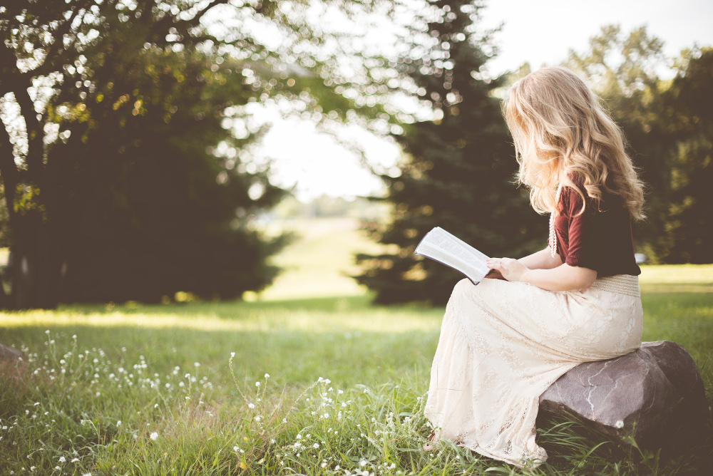 A woman reading a book in nature