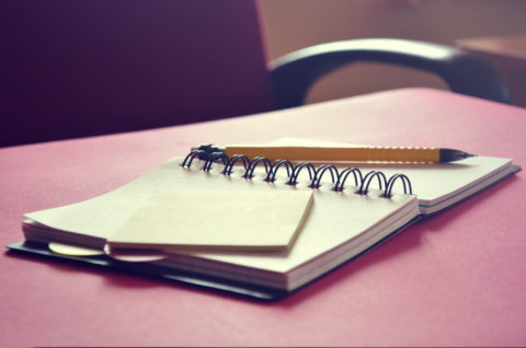 A notebook and a pen on a desk.