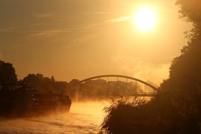 The sunset over a river. A boat is crossing, getting closer to a bridge.